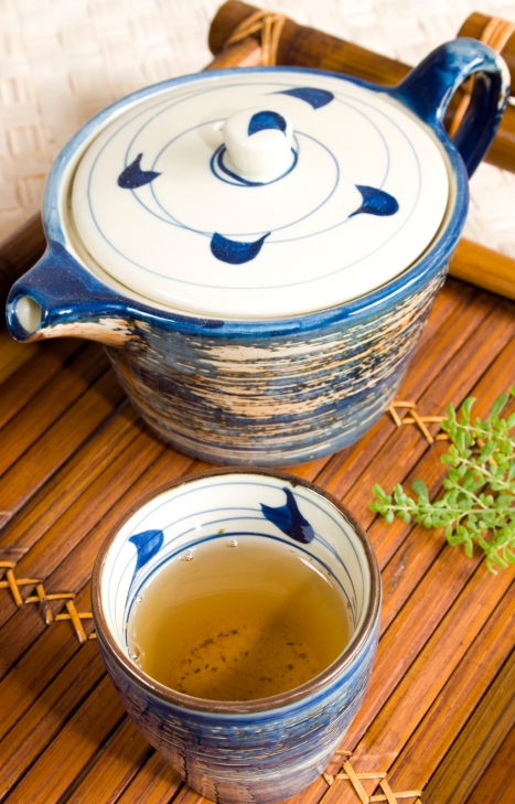 Feel Good Group - Teapot and mug of green tea on a bamboo tray.